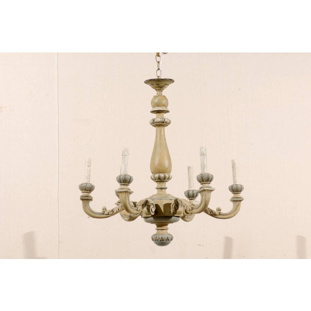 A French carved and painted wood six-light vintage chandelier. This French chandelier from the mid-20th century features a...