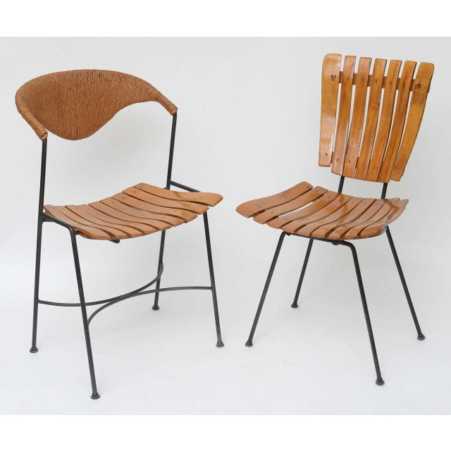 Set of four dining chairs by Arthur Umanoff for Raymor. All have black wrought iron bases and slatted wood seats....