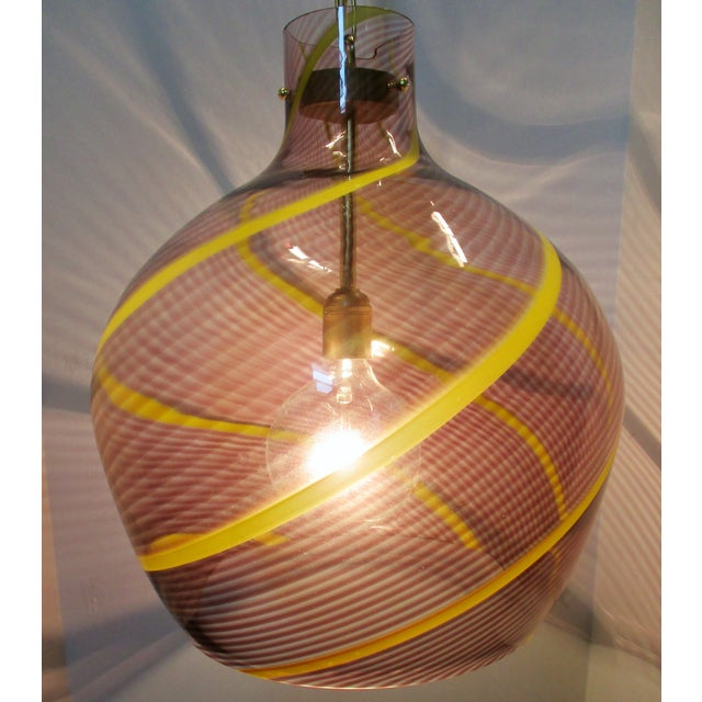 Oversize 1980s Italian blown glass pendant light in clear with aubergine and bright yellow tessuto technique. Light has...