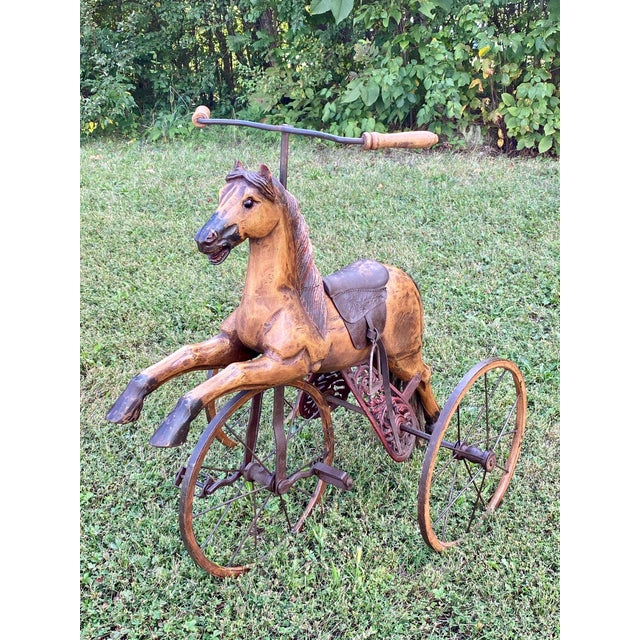 A charming reproduction horse bicycle having carved wood, leather saddle, iron wheels, glass eyes and rope tail. Child...