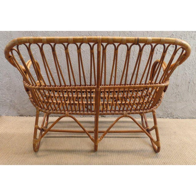 Boho Chic 1970s Italian bent rattan loveseat created in the manner of Franco Albini. The frame of the loveseat shows some...