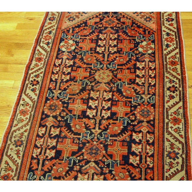 Handmade antique Malayer runner in red and blue shades. It is from the beginning of 20th century in original good...
