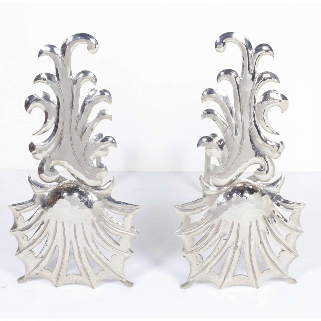 Pair of elegant vintage fireplace andirons with stylized shell design and wave patterns. Polished nickeled finish over...