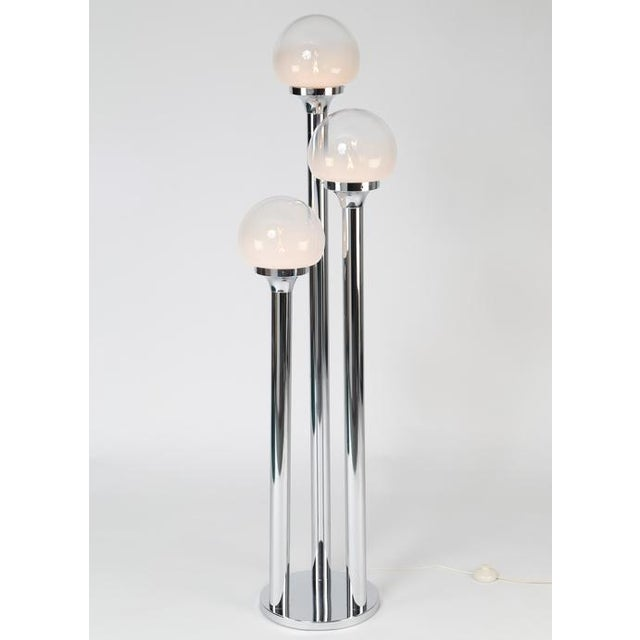 Polished-chrome floor lamp with three tubular supports, each holding a Murano-glass globe that is solid white at base...
