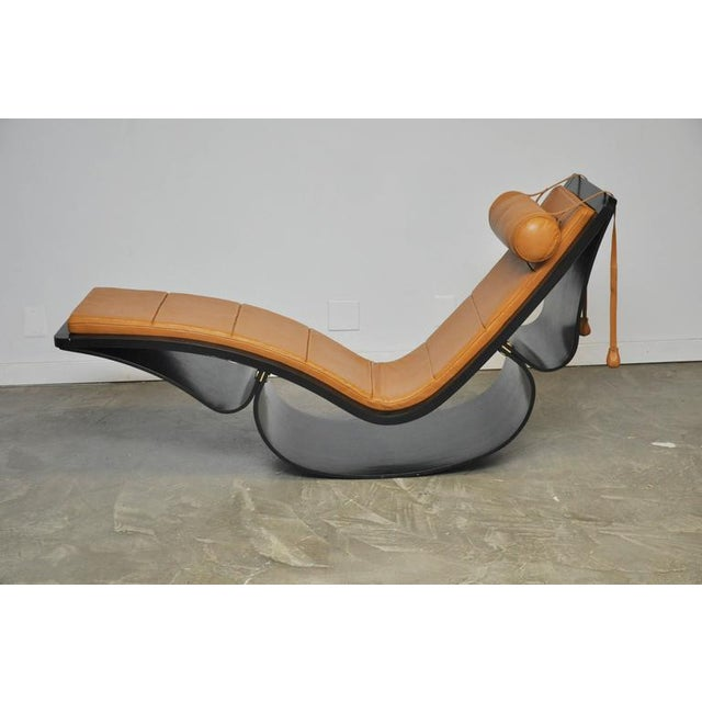 Sculptural rocking chaise longue in black painted laminated wood frame, brass fittings, and original tan leather...