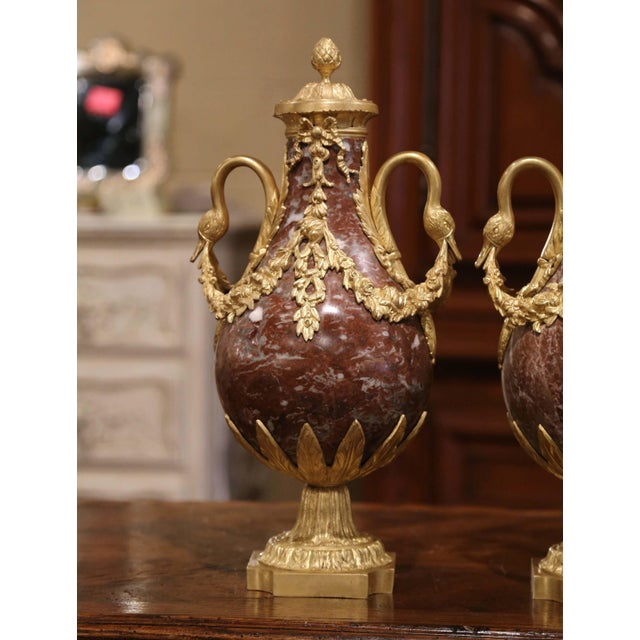 Crafted in France, circa 1870, these antique urns are made of marble and stand on square bronze bases decorated with leaf...