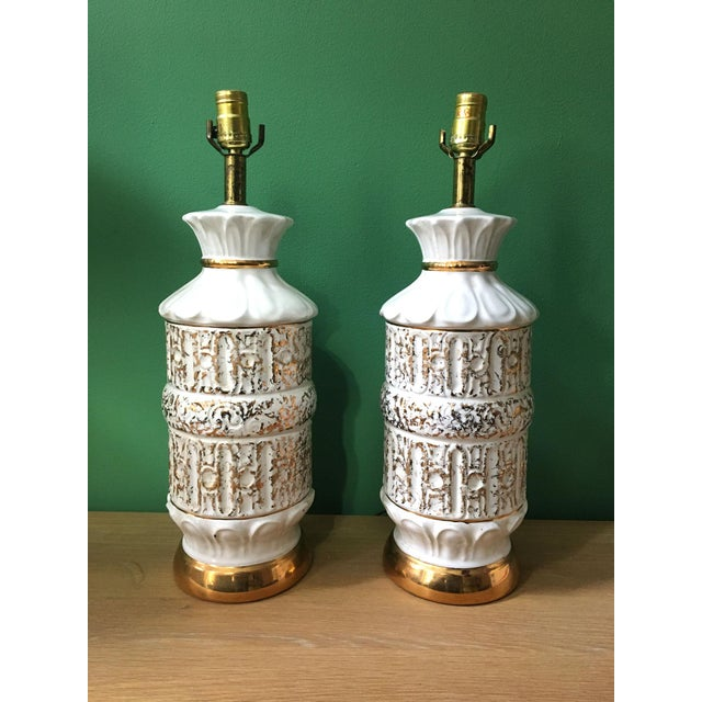 Pair of vintage table lamps, circa 1950s. White ceramic embossed pattern, lightly dusted with gold embellished texture....