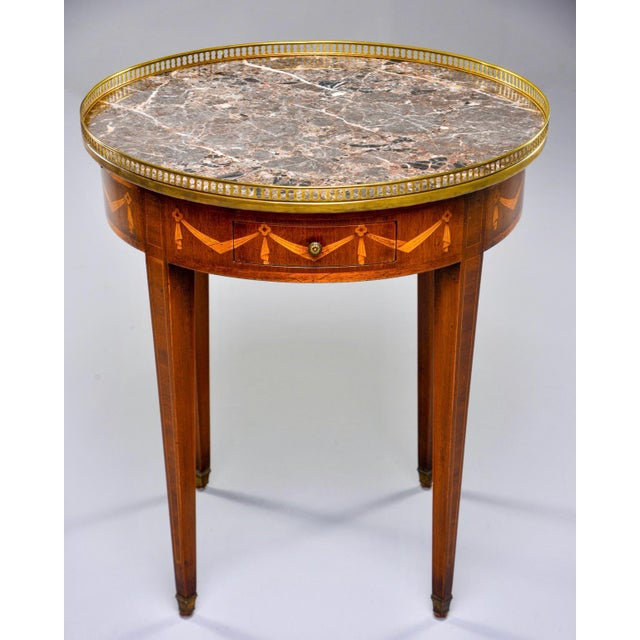Circa 1900 round French side table is made of oak with contrasting marquetry details of ribboned garland around the apron...