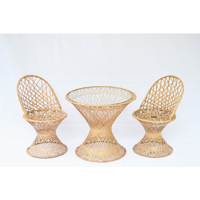 This mid-century modern rattan child's table and two chairs set is a rare and unique find in perfect condition. The table...