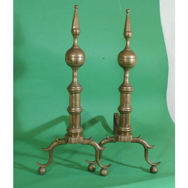 A handsome pair of brass andirons made in England or America about 200 years ago.
