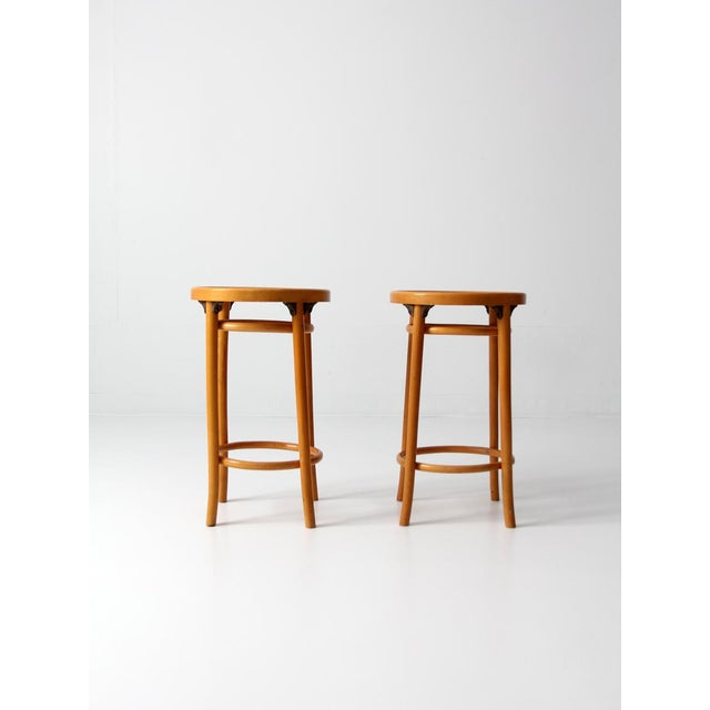 A set of two mid-century bentwood stools. The light brown wood stools feature slender shaped legs, bentwood ring center...