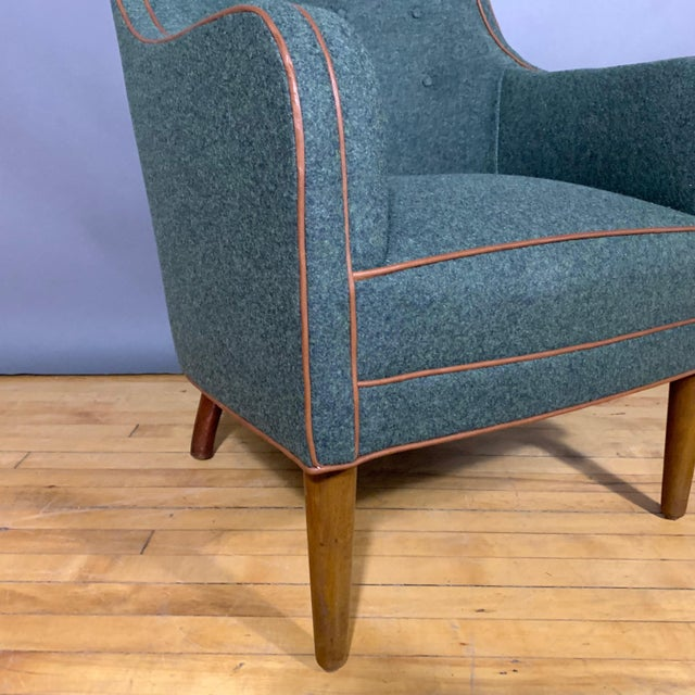 A perfectly proportioned armchair from Denmark 1950s with buttoned seat-back and a small scroll at top. On the diminutive...