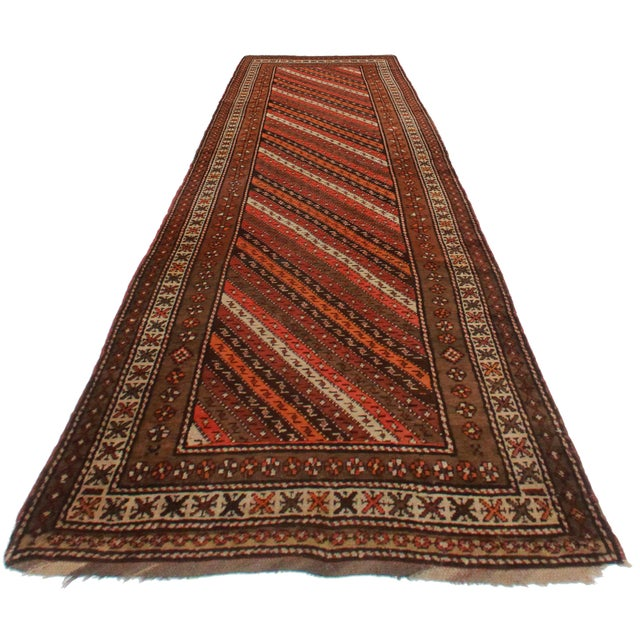 Offered is this antique Persian Hamedan runner. Hand-knotted from wool. A striped design in earth tones brings great...