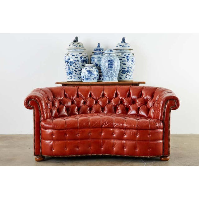 Stylish Mid-Century Modern English Chesterfield settee or loveseat featuring a rounded back kidney bean form. The kidney...