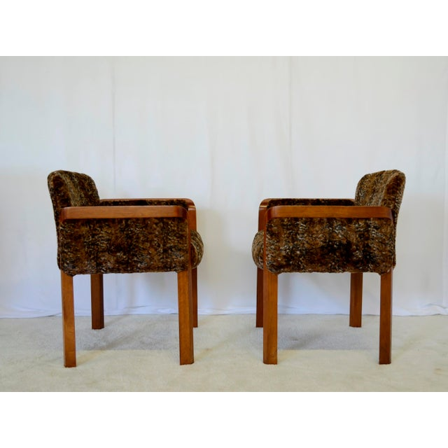 Pair of 1960's side chairs with curved wrap- around wood frame and sculpted legs and new padding and faux fur fabric. The...