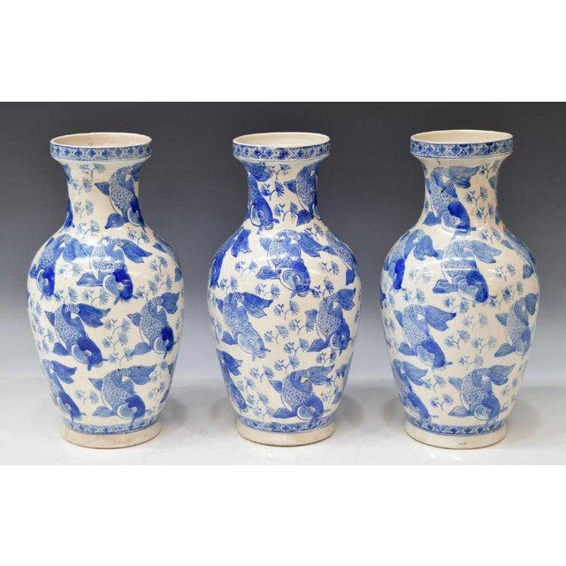 Set of three Chinese blue and white porcelain vases, 20th c. The repeated fish motif make the vase classic and fun! The...
