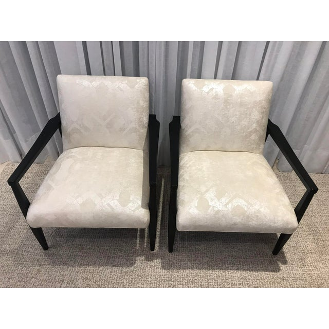 Pair of Arhaus Arm Chairs. Black painted frame with champagne colored upholstery. Two of the arms show minor wear and...