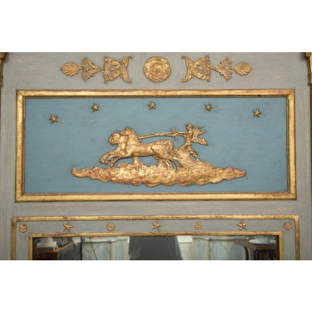 This is an exceptional blue-painted and parcel gilt French Empire trumeau with a gilt charioteer over a large mirror plate...