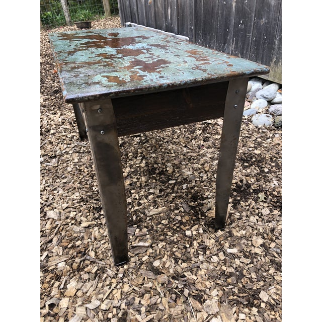A one of a kind industrial table having wooden top with copper tones underneath a distressed turquoise paint. The legs are...