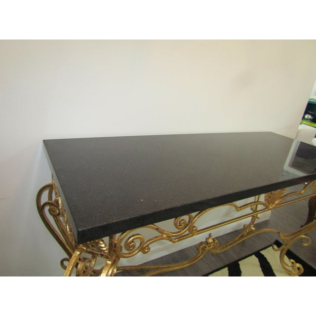 Stunning console table in gold leaf with a black granite top. The base is a decorative wrought iron recently covered in...