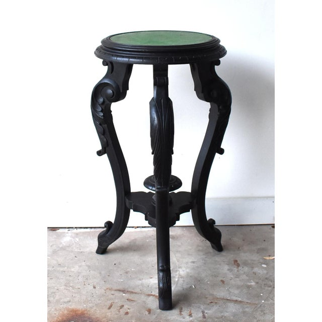 An antique French Napoleon III plant stand, fern pedestal, or gueridon table. Carved black ebonized wood with heavy...