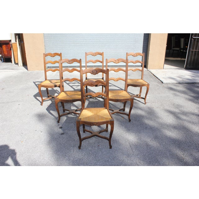 Set of six French country provincial ladder back chairs circa 1910s. Solid walnut Original rush seats. Crest rail with a...