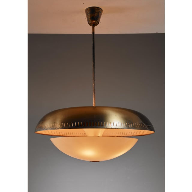 A Swedish pendant lamp, made of a perforated brass shade with a yellow glass diffuser underneath. The style is strongly...