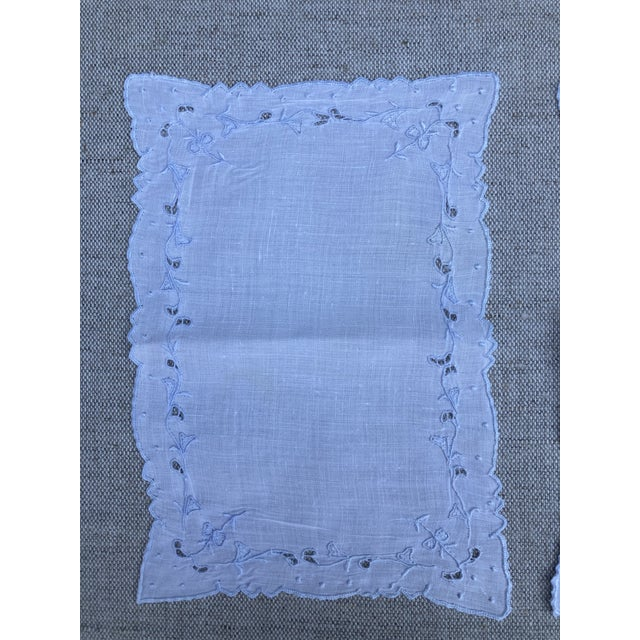 A set of 8 white linen cocktail napkins with pale blue embroidery, starched, pressed and ready to serve.