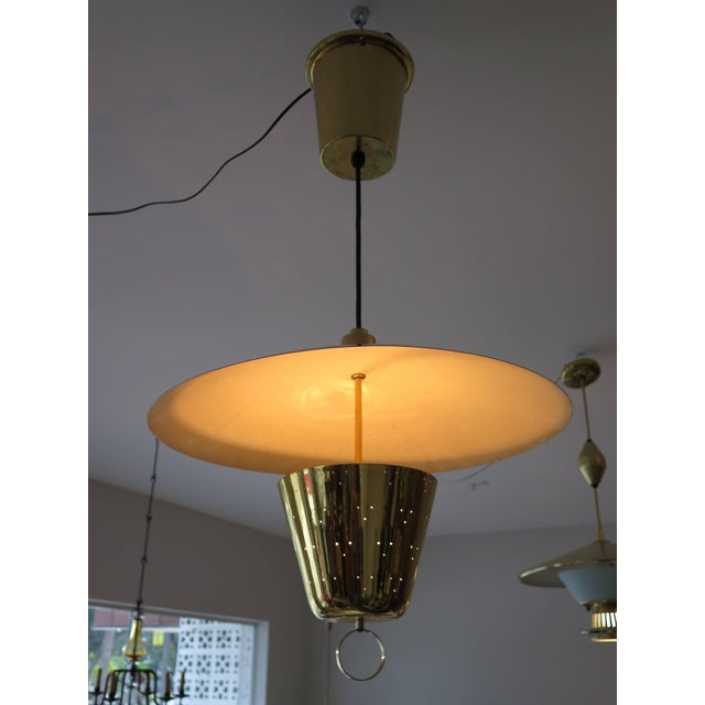 An unusual pendant lamp in polished brass attributed to Harry Gitlin for Ledlin Lighting Inc. Brass ring allows for easier...