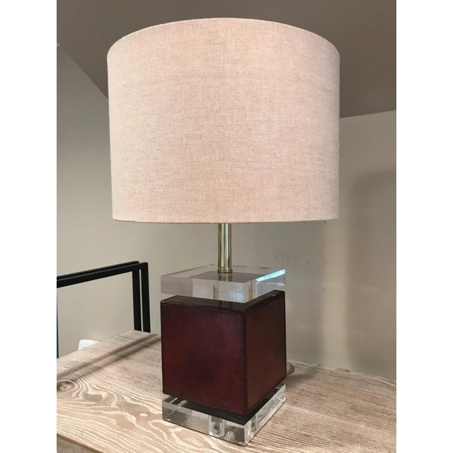 Ambassador Table Lamp with brown leather cube base on acrylic stand with tan linen shade. Bulb: Type A, 40 WATT Max (bulb...