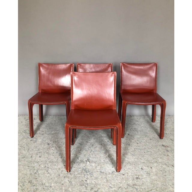 Offering a set of four beautiful Cassina CAB dining chairs in an oxblood red stitched saddle leather. Designed by Mario...