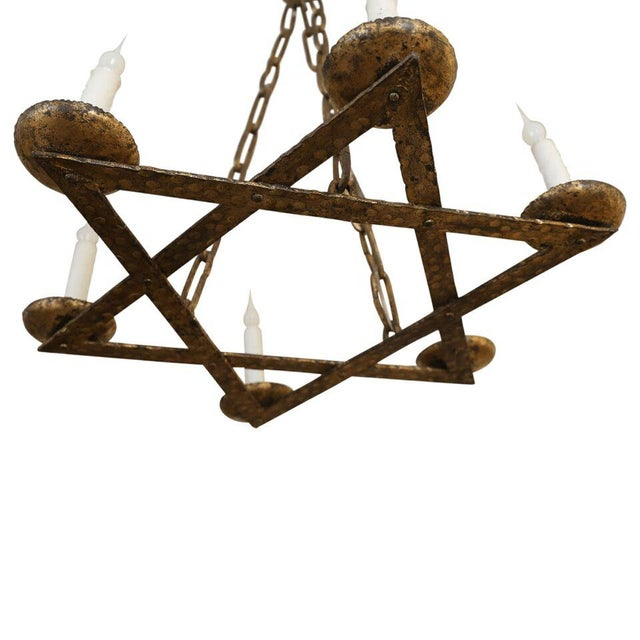 Fer doré star chandelier from Belgium, circa 1920-1940. Hand-wrought gilt-iron with original chain (up to the conical-...