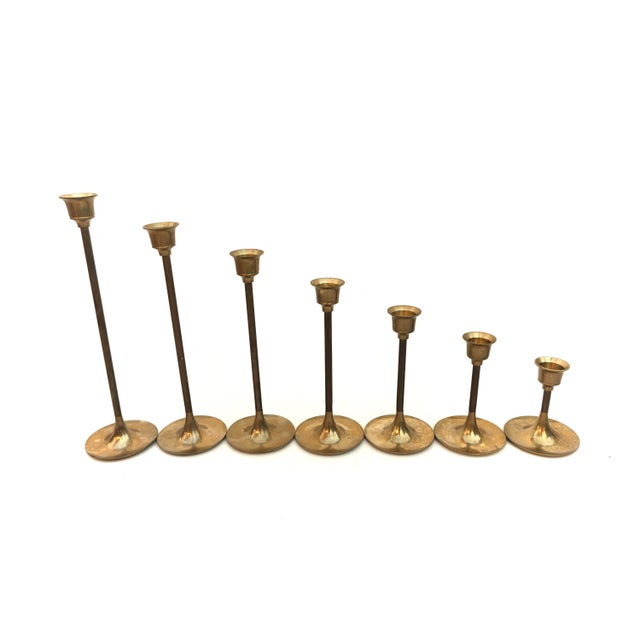 Cast an elegant glow on any occasion with this set of 7 chic vintage solid brass candlestick holders. Featuring slender...