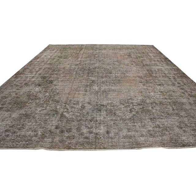 Distressed vintage Persian Tabriz rug with rustic farmhouse style. This distressed vintage Persian rug features variegated...