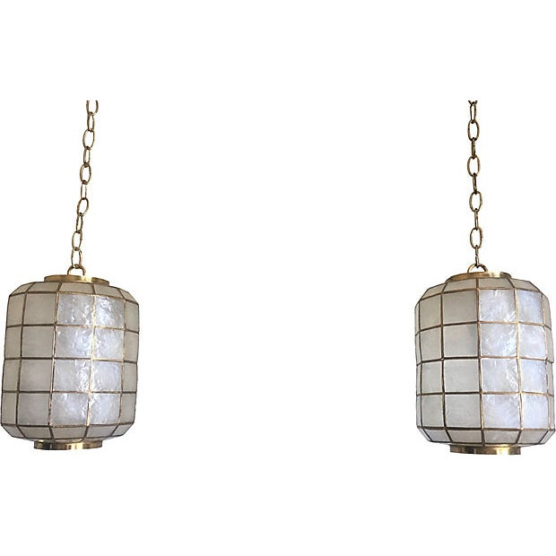 Rare and lovely pair of mid-century capiz shell lanterns imported from the Philippines with brass overlay and finials. One...
