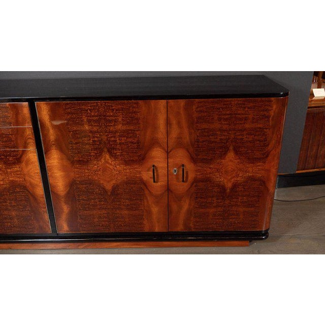 This refined Art Deco Machine Age sideboard was realized in the United States, circa 1935. It features a streamlined body...