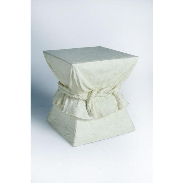 A chic occasional table in a square pedestal shape with a cinched rope drapery effect and a faux plaster off-white finish....