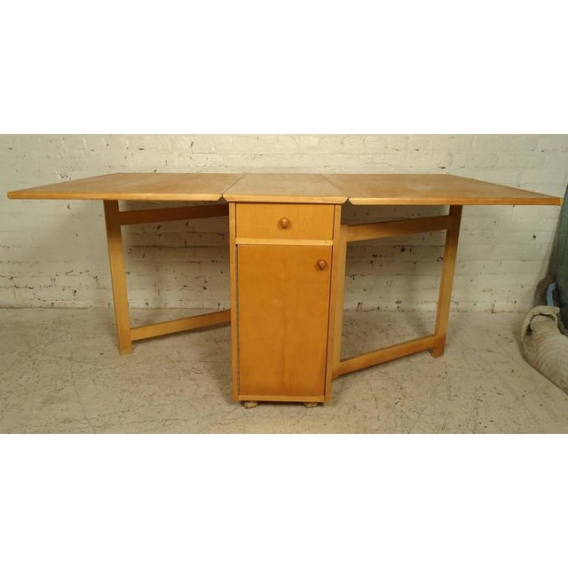 Vintage dining set and four folding chairs. The chairs stow away inside the table perfectly. Table also features one-...