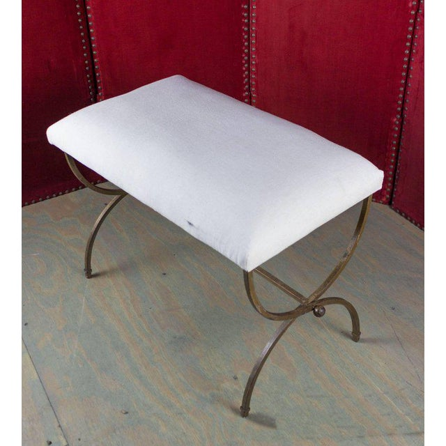 Spanish gilt iron bench with ball detail and upholstered seat.