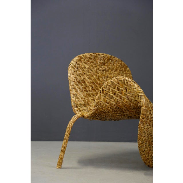 Mid-Century Italian armchair in 1950 rattan. The armchair has a beautiful butterfly design and is very fashionable in this...