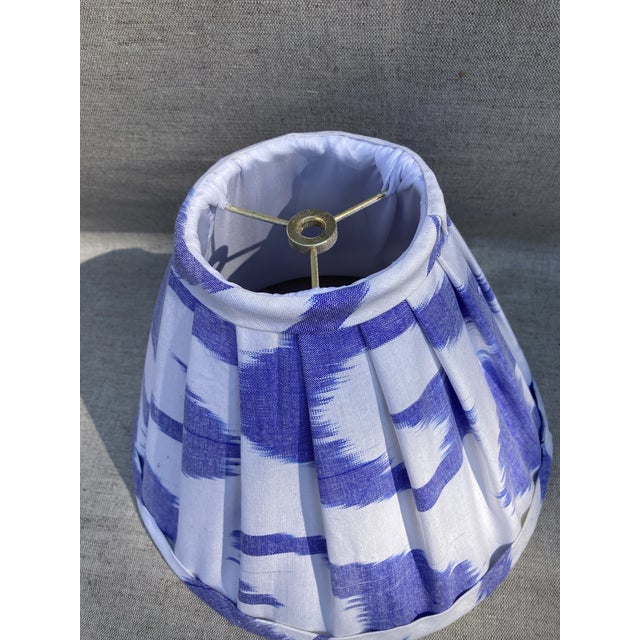 """A pleated lampshade handmade with a blue and white cotton Ikat fabric. Measurements: top 4"""" side 9"""" bottom 11"""""""