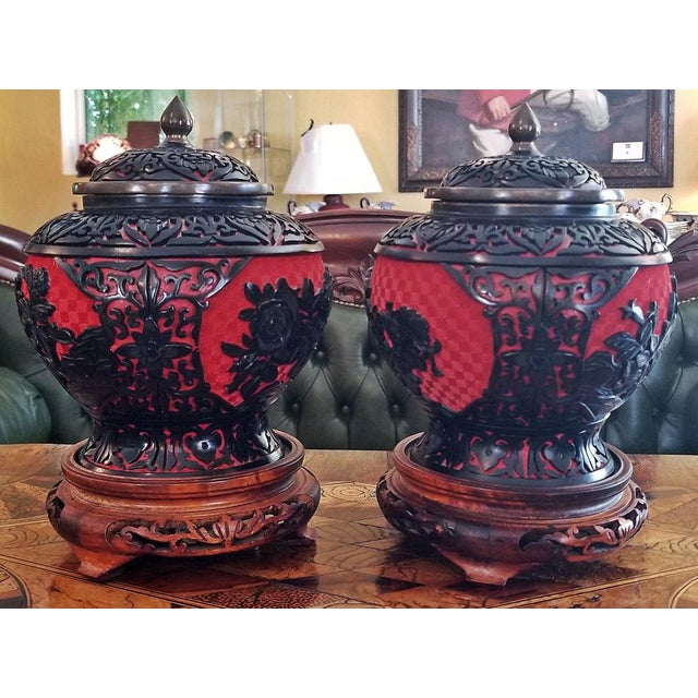 Gorgeous pair of early 20th Century Chinese cinnabar lacquer and enameled lidded urns or vases on wooden stands. Each urn...