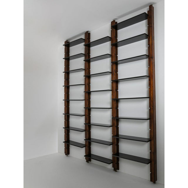 Large modular bookcase composed by movable black painted shelves and wood uprights with brass feet. More uprights and...