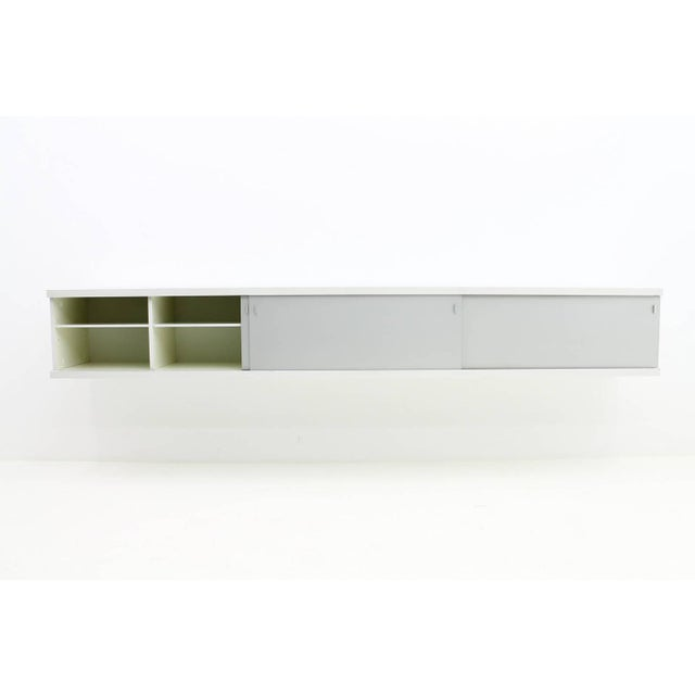 Long wall-mounted sideboard with three aluminum sliding doors by Horst Bruning, 1960s. Measures: W 310 cm, H 45 cm, D45...