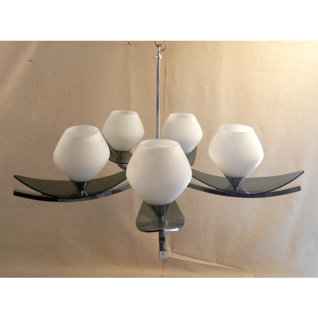 Stunning mid-century chrome chandelier. Diffused light from the five white glass globes and tinted lucite leaves creates a...