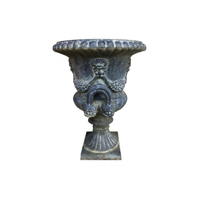 This cast iron jardiniere of classic campana or bell-shaped urn form features a gadrooned edge, raised neoclassical swags...
