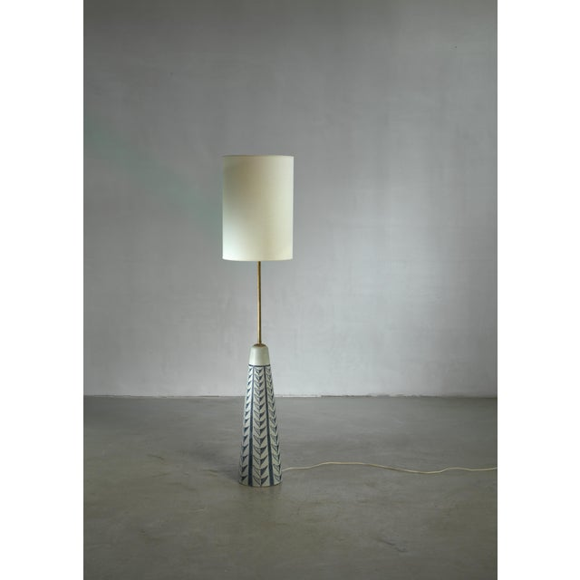 A ceramic floor lamp with a long brass stem, designed by Rigmor Nielsen for Søholm. The measurements stated are of the...