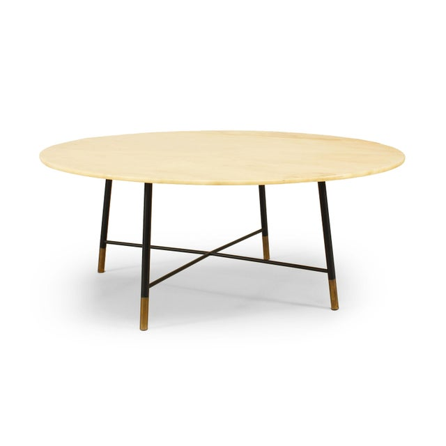 Italian Mid-Century Modern coffee table with four ebonized metal legs and stretcher with brass feet supporting a round...