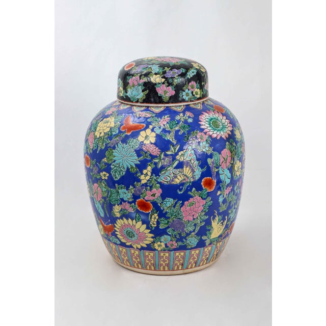 This vibrant blue famille rose lidded urn features a multitude of flowery blooms, along with a band of symbols...