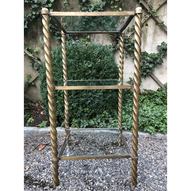 Pair of modern brass and glass tiered etageres. Comprised of three shelves with inset glass flanked by barely twist...